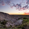 A vibrant sunrise over the plains of Badlands National Park.- Badlands National Park