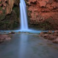 A long exposure of Havasu Falls as swimmers enjoy the waters.- Havasu Falls Hike via Havasupai Trail