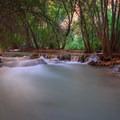 Havasu Creek cascades over limestone travertines through the campground.- Havasu Falls Hike via Havasupai Trail