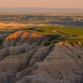 Green plains top the erosional formations of Badlands National Park.- Badlands National Park