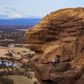Climbers ascend Monkey Face with Mount Jefferson on the horizon.- Smith Rock State Park