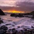 The sun sets on the distant horizon as waves pour over the rocky coast of Luffenholtz Beach.- Luffenholtz Beach