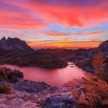 Vibrant sunrise over Perfection Lake as golden larches look on.- Enchantment Lakes Hike via Colchuck Lake
