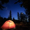 An illuminated tent in Paradise Park as the moon is about to set.- Timberline Trail