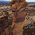 Climbers ascend Monkey Face with Mount Jefferson on the horizon and the Crooked River far below.- Smith Rock, Misery Ridge Hiking Trail