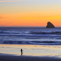 A beach walker enjoys the sunset with Pyramid Rock off-shore.- Cape Meares Big Spruce + Beach Trail