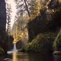 Sun rays cut through the mist from Punchbowl Falls.- Columbia River Gorge National Scenic Area