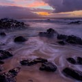 Colorful sunset as waves crash over the rocks north of the lookout.- Ho'okipa (H-Poko) Beach Park + Overlook
