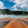 Breaks in the wind let you see the rainbow colors of Grand Prismatic Spring.-  Hot Springs, Geysers, and Other Geothermal Activity