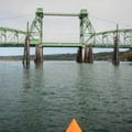 Paddling upstream under the Coquille River Bridge.- Favorite Estuaries + Lakes to Paddle on the Oregon Coast