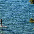 A young stand-up paddleboarder enjoying the clear waters off of Rubicon Point.- The Beaches of Tahoe