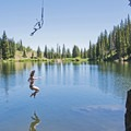 Taking the drop from the rope swing at Bloods Lake.- Incredible Lakes to See this Summer