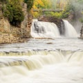 Rainbow Falls surrounded by fall colors in Ausable Chasm.- Breathtaking Cliffside Vistas