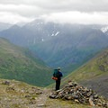 Hiker looking north down the Raven Creek Valley from the Crow Pass Trail.- Our Guide to Epic Alaskan Summer Explorations