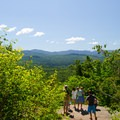 A family enjoys the view from the summit of Cobble Hill.- 15 Must-see Fall Foliage Adirondack Adventures