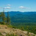 A lone hiker takes in the view from the lookout.- 15 Must-see Fall Foliage Adirondack Adventures