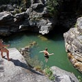 A cliff jumper takes the plunge into Devil's Punchbowl, Colorado.- Plunge Into Swimming Holes