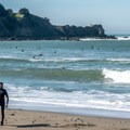 Surfers at Linda Mar, Pacifica State Beach, south of San Francisco.- Best West Coast Beaches for Beginner Surfers