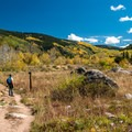 Reading the trail signs at the Tenth Mountain Bridge in Colorado.- The Best Leaf-Peeping Adventures for Fall Foliage