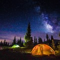 A quintessential camp shot, lit up tents with the Milky Way above. - Photography Essentials: Night Shooting + Astrophotography