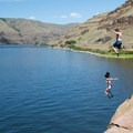 Two bathers make the jump at the cliff above Granite Point.- Washington's 50 Best Swimming Holes