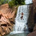 Jumping into a waterfall at Mill Creek.- Backcountry Swimming Holes Worth the Effort