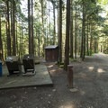 Vault toilet and garbage/recycling at Bench Campground.- Sasquatch Provincial Park