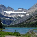 A stunning view of Lake Josephine with the Garden Wall and waterfalls in the distance.- Glacier National Park