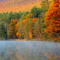 A view of Lake Shaftsbury and one of the trail bridges from the beach in autumn.- Great American Towns for Fall Foliage
