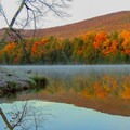 Lake Shaftsbury in Vermont is bursting with color during the fall.- 8 Unique Fall Camping Trips