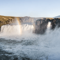 A rainbow bridges the waterfall in the summer.- Guide to Iceland's Ring Road