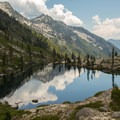 Clouds and mountains reflect in the Lower Canyon Creek Lake.- Hiking in the Trinity Alps
