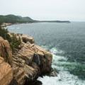 Climbers grouped at the top of Otter Cliff in Acadia National Park.- Otter Point + Otter Cliffs