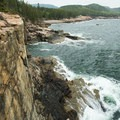 Waves crash at the base of a popular climbing route on Otter Cliffs in Acadia National Park.- Otter Point + Otter Cliffs