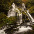 Warm autumn colors provide a welcoming glow to the scene.- Panther Creek Falls