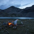 A hiker enjoys the beginnings of a small campfire.- Broad Canyon: Betty, Goat + Baptie Lakes and the Surprise Valley Divide