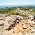 From the summit of Cadillac Mountain, enjoy views of sprawling fall foliage against the blue Atlantic waters.- Ultimate Leaf-Peeping Road Trip through New England