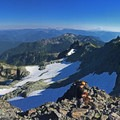 A panoramic view from the summit of Unicorn Peak. Contributor Josh Lupkin is setting up the rappel rigging on the summit tree.- Unicorn Peak via Snow Lake
