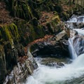 The beauty of Honey Hollow Falls in Vermont is enhanced in the fall by colorful leaves.- 15 Stunning Photos to Inspire a Fall Trip to New England