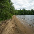 A beach at one of the campsites.- 12 New York Lakes Perfect for Summer Adventure