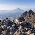 Mount Bachelor looms in the distance beyond Broken Top's alternate summit.- Broken Top