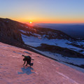 A climber ascends a steep snowfield at dawn.- The Pacific Northwest