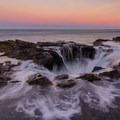 Waves churn as the sun rises over Thor's Well.- Thor's Well + Cook's Chasm