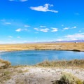 Emerald waters sparkle beneath blue skies at Ruby Valley Hot Springs.-  Hot Springs, Geysers, and Other Geothermal Activity