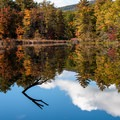 Fall reflections on Lake Shaftsbury in Vermont.- The Best Leaf-Peeping Adventures for Fall Foliage