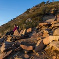 Hikers relax on stone furniture at the Living Room. - Wildflower Hikes Near Salt Lake City, Utah