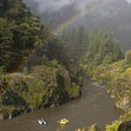 A rainbow over boats in Huggins Canyon along the Rogue River.- Must-Do Rafting Trips in the West