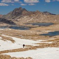 A JMT hiker climbing toward Muir Pass (11,955 feet) with Lake McDermand, Wanda Lake and Mount McGee in the background.- John Muir Trail (JMT) Overview