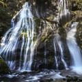 The full Panther Creek falls from below on a sunny day.- Waterfalls on the Washington Side of the Columbia River Gorge