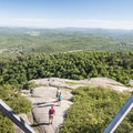 Looking down at some hikers from the Poke-O-Moonshine Mountain fire tower.- Incredible Adirondack Hikes Below 4,000 Feet